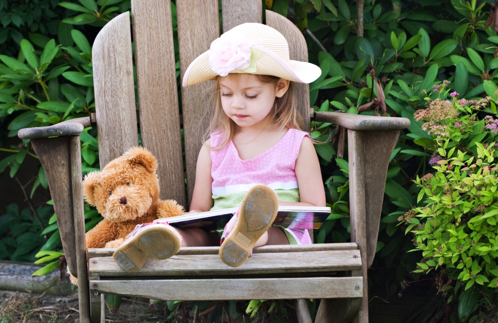 girl reading with teddy bear